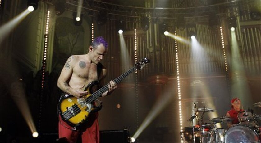 A foot injury has led Red Hot Chili Peppers to postpone its 2012 winter tour, including its sold-out Feb. 28 San Diego show, which has been re-scheduled for September. The Los Angeles band is among the artists who will be inducted into the Rock and Roll Hall of Fame's Class of 2012 this year. (AP Photo/Peter Morrison)