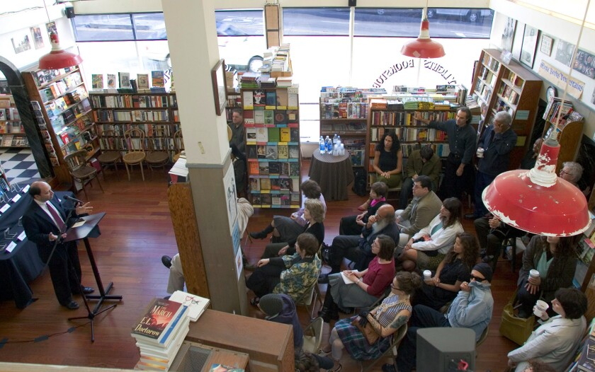 Harold Augenbraum, left, executive director of the National Book Foundation, announces the National Book Award finalists at San Francisco's City Lights Bookstore in 2006.