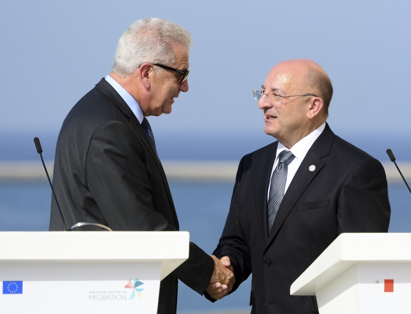 EU commissioner for migration Dimitris Avramopoulos, left, shakes hands with Maltese Interior Minister Michael Farrugia during a joint press conference at the end of an informal meeting of EU interior ministers, at Fort St. Angelo, in Birgu, Malta, Monday, Sept. 23, 2019. Five European Union nations have agreed to a temporary arrangement to take in migrants rescued from the central Mediterranean Sea. (AP Photo/Jonathan Borg)