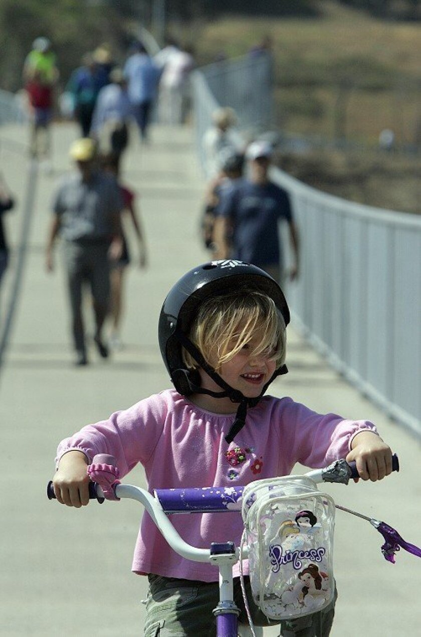Cassiella Brown, 4, of Encinitas, rides her training wheel-equipped bicycle across the new bridge Friday morning.
