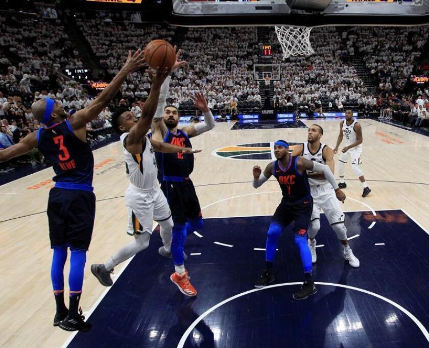 El jugador de los Utah Jazz Donovan Mitchell (2i) lucha por el balón con Corey Brewer (i) y Steven Adams (c-i) de los Oklahoma City Thunder durante el partido de la NBA entre Utah Jazz y los Oklahoma City Thunder en el Vivint Smart Home Arena en Salt Lake City en Utah (Estados Unidos) el 23 de abril de 2018. EFE