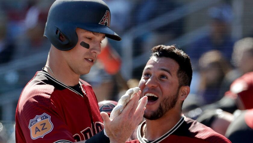 The Diamondbacks' A.J. Pollock, left, celebrates with David Peralta after scoring on a single by Paul Goldschmidt during the first inning of a spring baseball game in Scottsdale, Ariz., Saturday, Feb. 25, 2017.