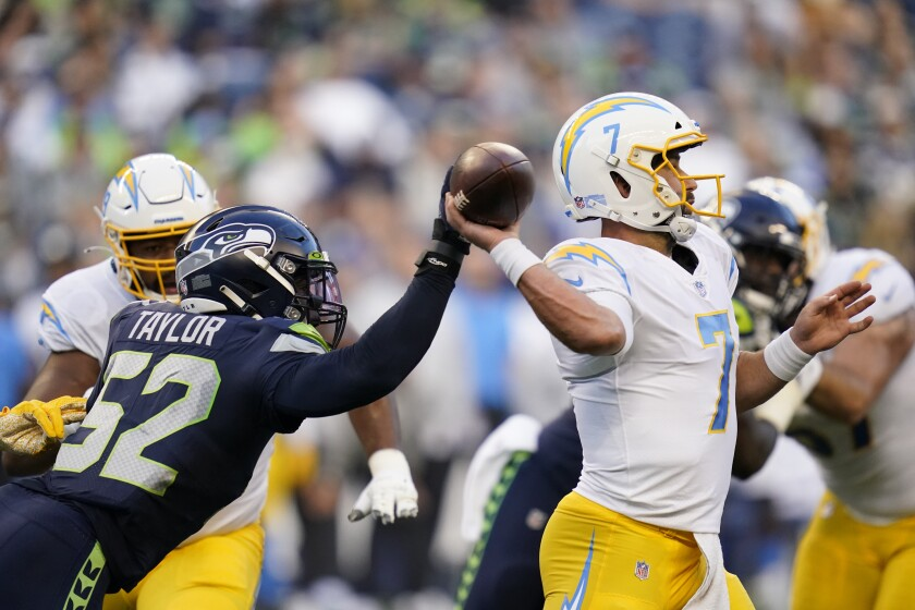 Seahawks defensive end Darrell Taylor reaches for the ball as Chargers quarterback Chase Daniel passes Aug. 28, 2021.