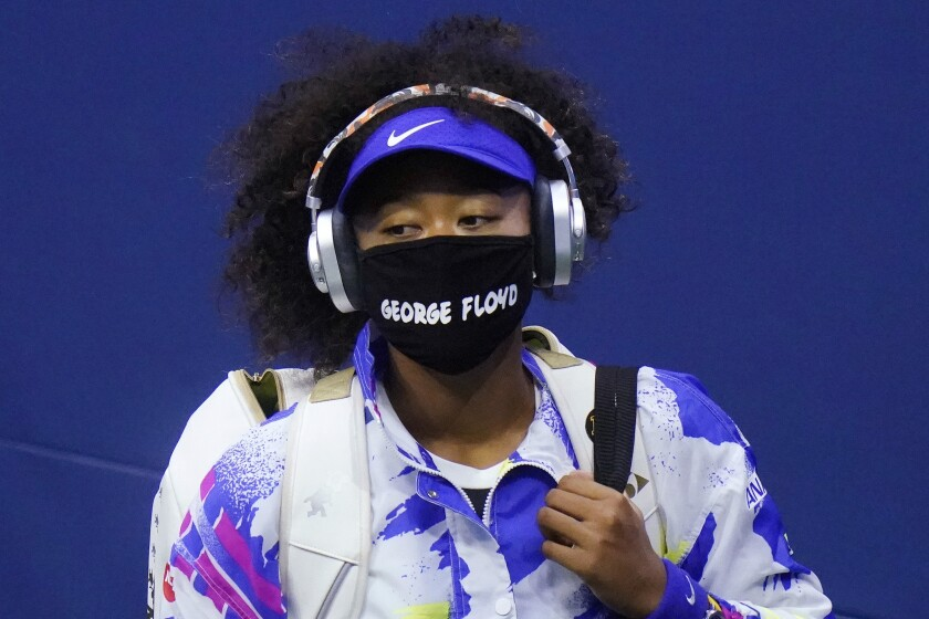 """FILE - In this Sept. 8, 2020, file photo, Naomi Osaka, of Japan, wears a protective mask due to the COVID-19 virus outbreak, featuring the name """"George Floyd"""", while arriving on court to face Shelby Rogers, of the United States, during the quarterfinal round of the US Open tennis championships, in New York. Osaka's victory in the U.S. Open helped raised the issue of racial injustice in the United States. Before each of her matches, she wore a mask with the names of seven Black Americans who died as victims of violence.(AP Photo/Frank Franklin II, File)"""
