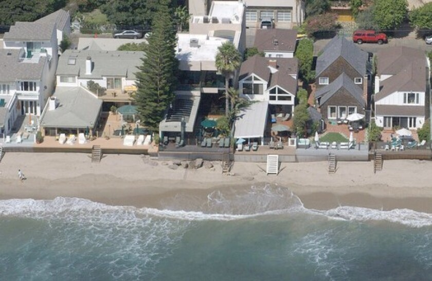 The Malibu Colony beach home, third house from left with a dark patio, was last owned by Lawrence and Linda Elins. The home's value was recorded at $12 million when the property was transferred May 13, 2009, to Wells Fargo Bank.
