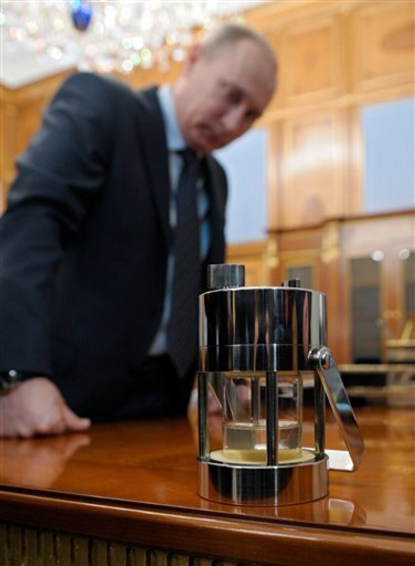 Russian Prime Minister Vladimir Putin examines a canister during a meeting with natural resources and ecology minister Yuri Trutnev in Moscow on Friday, Feb. 10, 2012. Natural resources and ecology minister Yuri Trutnev presented Putin with a canister containing water taken from the boreshaft drilled to Lake Vostok under Antarctica.(AP Photo/RIA Novosti, Alexei Nikolsky, Government Press Service)
