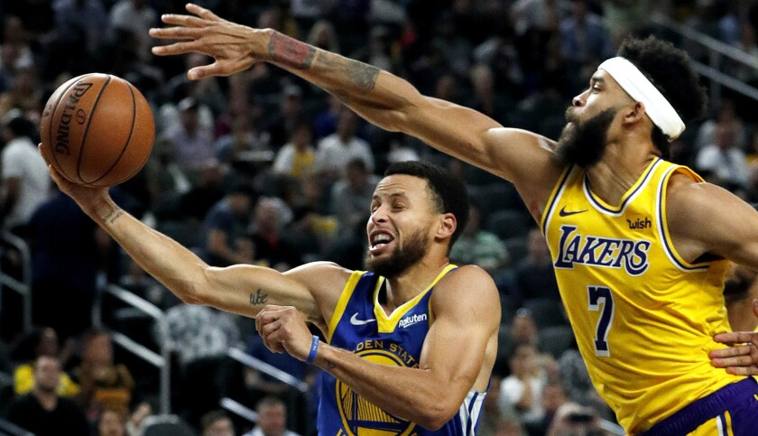 Golden State Warriors guard Stephen Curry shoots around Los Angeles Lakers center JaVale McGee durin