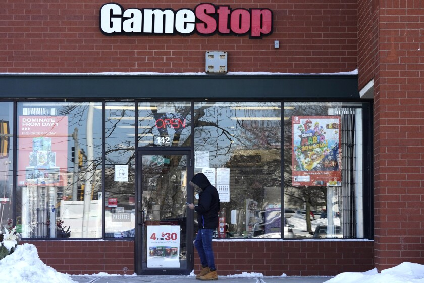 FILE - In this Jan. 28, 2021 file photo, a customer checks on his cellphone as he walks to a GameStop store in Vernon Hills, Ill. The frenzy around GameStop's stock may have quieted down, but the outsized influence small investors had in the saga is likely to stick around. While no one expects another supernova like GameStop, the tools that smaller investors employed to supercharge its stock can be used again and again. (AP Photo/Nam Y. Huh, File)