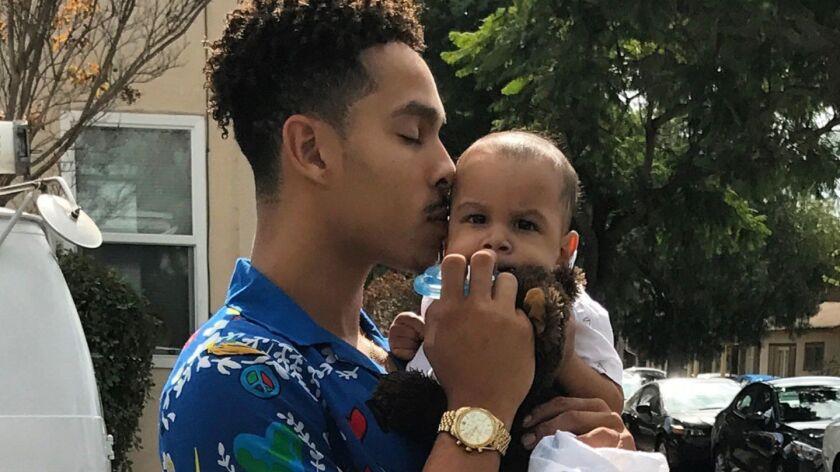 Former Pasadena basketball player Ajon Efferson holds his son, Phoenix.