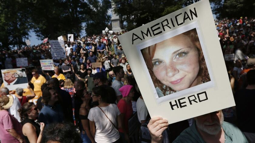 """A counter-protester holds a photo of Heather Heyer at a """"Free Speech"""" rally organized by conservative activists in Boston on Aug. 19, 2017."""