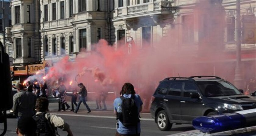 Participants of an unsanctioned protest against Prime Minister Vladimir Putin  light up flares and colored smoke devices at Triumfalnaya (Triumph) Square in downtown Moscow, Russia, Sunday, May 31, 2009. Russian police detained banned National-Bolshevik Party leader Eduard Limonov and several other