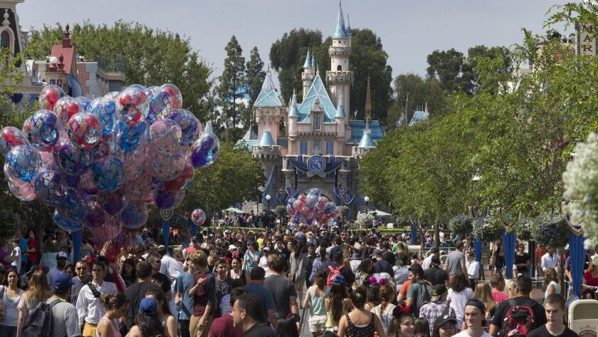 """A large crowd strolls down Main Street during Disneyland's diamond jubilee celebration in June 2015. A petition to require major employers who receive city subsidies to pay a """"living wage"""" has qualified for the Anaheim ballot."""