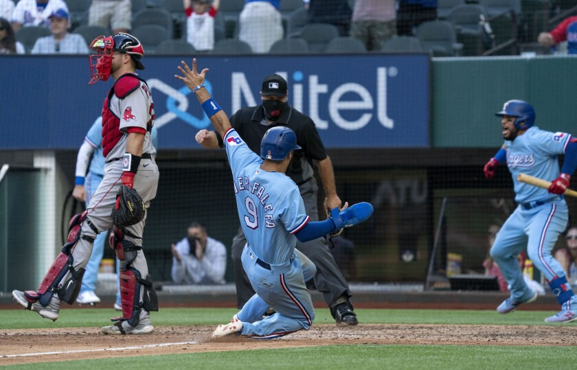Texas Rangers' Isiah Kiner-Falefa (9) scores on a go-ahead RBI single by Brock Holt as home plate umpire Brian O'Nora and Boston Red Sox catcher Kevin Plawecki look on while Texas Rangers' Willie Calhoun celebrates in the background during the eighth inning of a baseball game Sunday, May 2, 2021, in Arlington, Texas. (AP Photo/Jeffrey McWhorter)