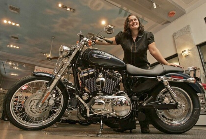Emily Vindeni, controller of the Harley-Davidson shop in Glendale, poses with a Sportster, Harley's smallest, least expensive bike. Sales are slow for the costly touring models but Sportster demand is healthy.