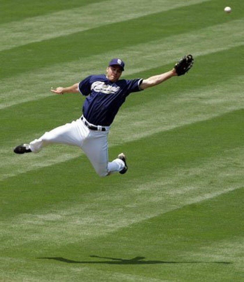 The Padres' Craig Stansberry can't make a catch of a hit by the Minnesota Twins' Mike Redmond in the fourth inning Thursday at Petco Park.
