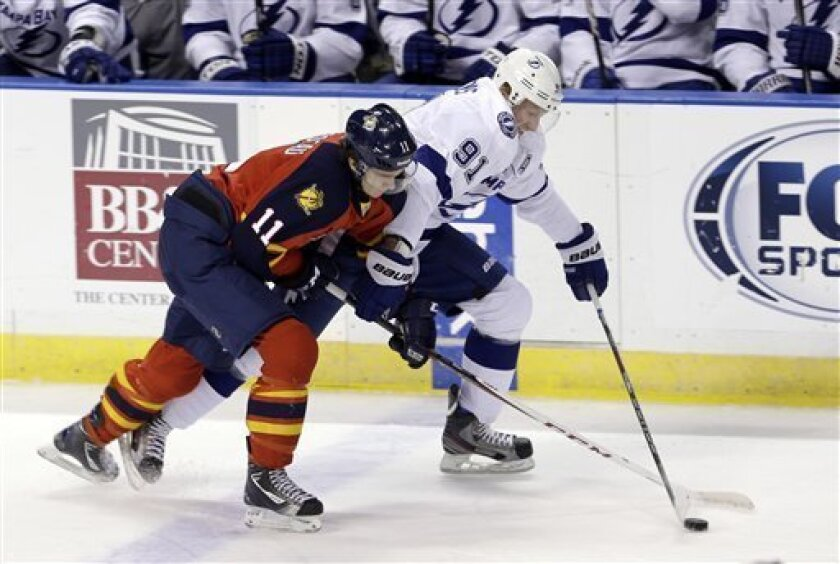 Florida Panthers' Jonathan Huberdeau (11) checks Tampa Bay Lightning's Steven Stamkos (91) in the second period of an NHL hockey game in Sunrise, Fla., Saturday, Feb. 16, 2013. (AP Photo/Alan Diaz)