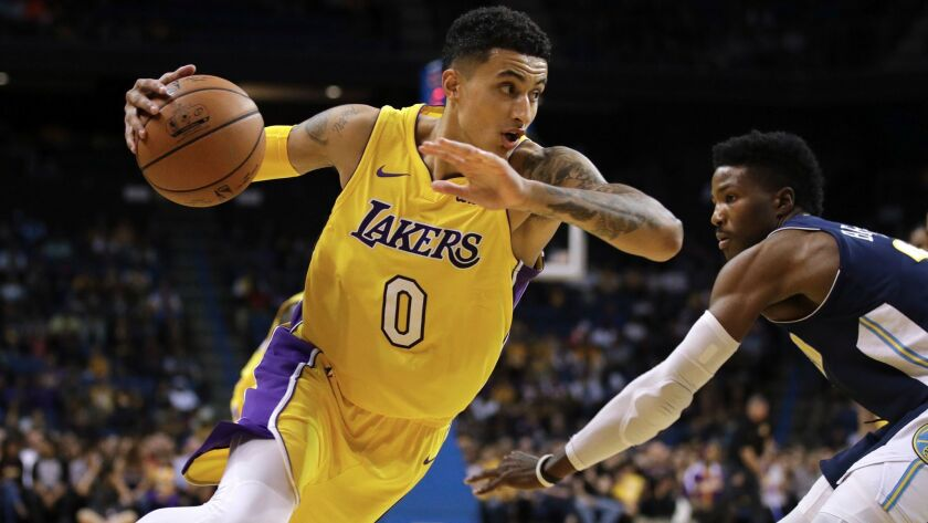 The Lakers' Kyle Kuzma, left, dribbles past Denver's Malik Beasley during a preseason game in Ontario on Oct. 4.