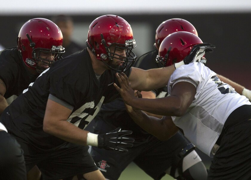 SDSU #64 Zach Dilley of the offensive line battles against #93 Malcolm Jackson during drills Monday night during practice at SDSU.