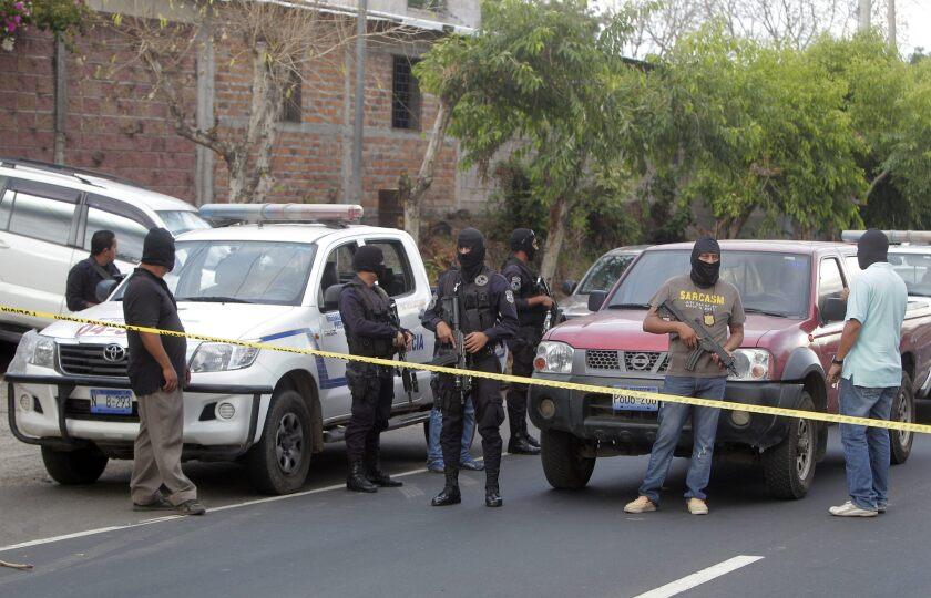 Agentes de la Policía Nacional Civil (PNC) permanecen en las cercanías de la escena de la masacre, en Quezaltepeque, donde murieron nueve personas.