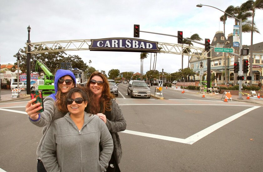 Brooke Price (left), Mireya Barajas and Abby Snyder take a selfie of themselves with the new sign over Carlsbad Boulevard at Carlsbad Village Drive on Tuesday. They all work together at the Carlsbad Boys & Girls Club and are happy with the new sign.