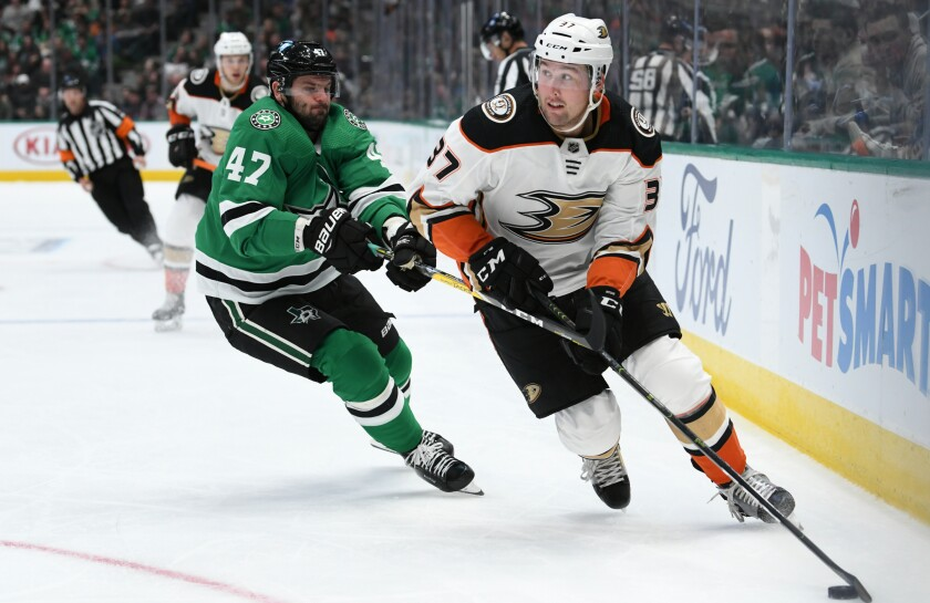 Ducks forward Nick Ritchie controls the puck ahead of Dallas Stars forward Alexander Radulov during the Ducks' 2-1 loss.