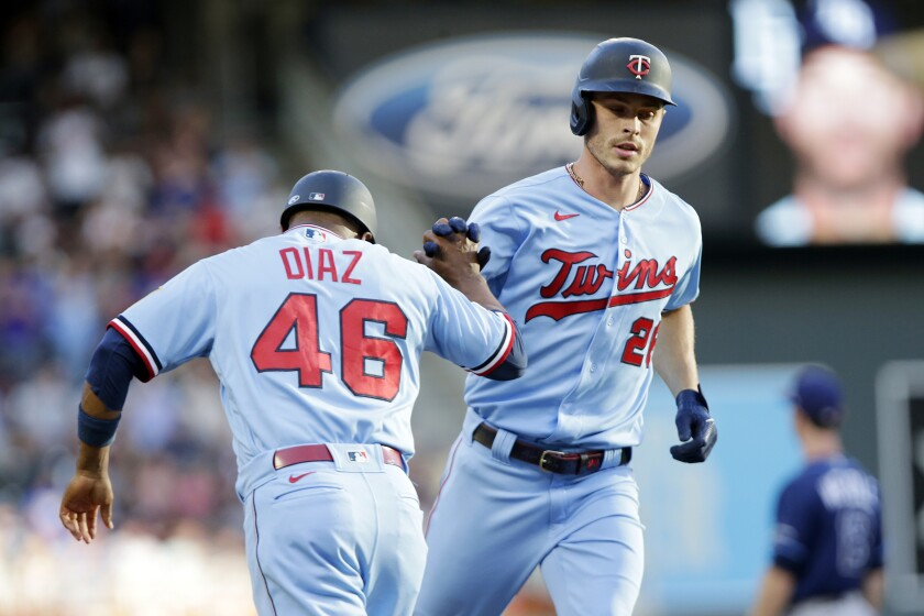 Minnesota Twins' Max Kepler (26) is congratulated by Minnesota Twins third base coach Tony Diaz (46) on his home run against the Tampa Bay Rays in the first inning of a baseball game, Saturday, Aug. 14, 2021, in Minneapolis. (AP Photo/Andy Clayton-King)