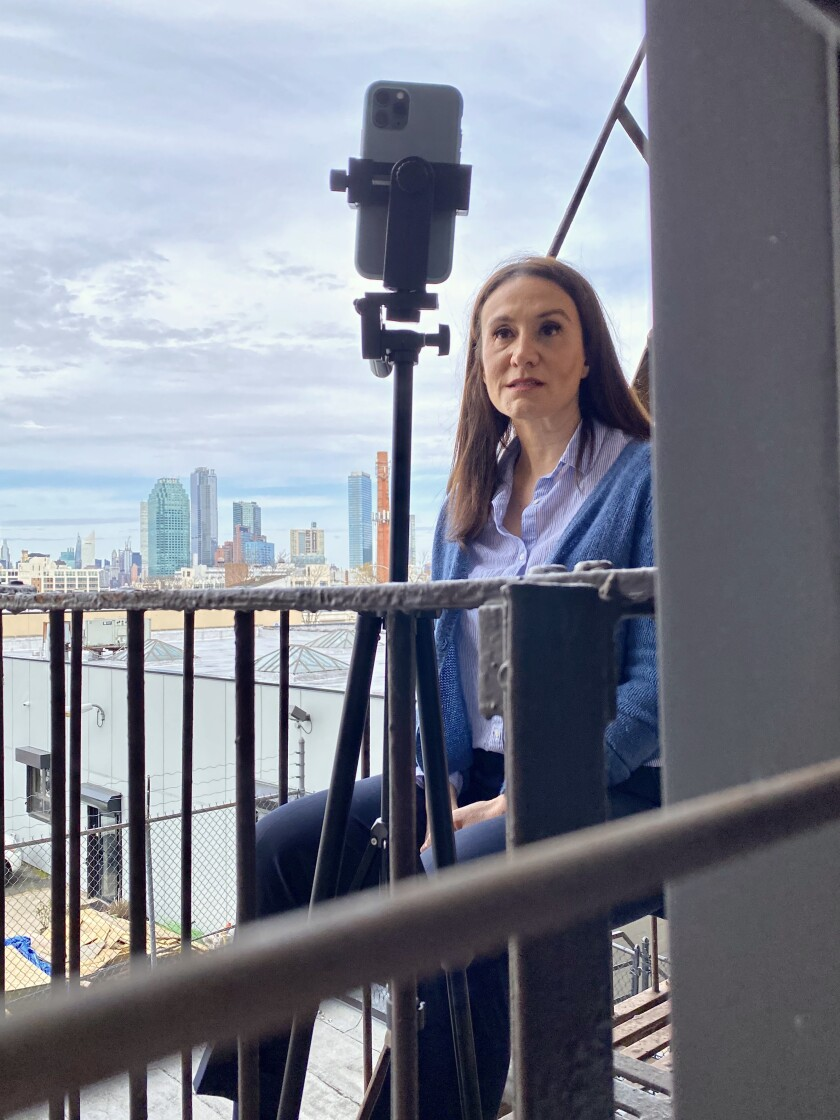 Michelle Caruso-Cabrera shoots a campaign video on the fire escape of her apartment in Queens, N.Y.