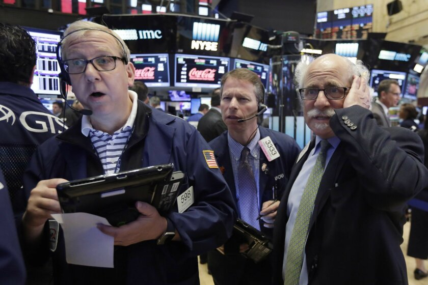 Traders Richard Cohen, left, Robert Charmak, center, and Peter Tuchman, work on the floor of the New York Stock Exchange, Friday, June 3, 2016. Stocks are broadly lower in early trading and bond prices are higher after the government reported a sharp slowdown in hiring last month. (AP Photo/Richard
