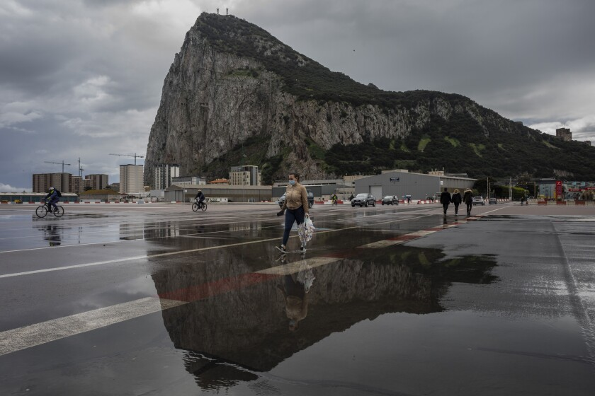 """People cross the Gibraltar airport runway towards the border crossing with Spain, backdropped by the Gibraltar rock, in Gibraltar, Friday, March 5, 2021. Gibraltar, a densely populated narrow peninsula at the mouth of the Mediterranean Sea, is emerging from a two-month lockdown with the help of a successful vaccination rollout. The British overseas territory is currently on track to complete by the end of March the vaccination of both its residents over age 16 and its vast imported workforce. But the recent easing of restrictions, in what authorities have christened """"Operation Freedom,"""" leaves Gibraltar with the challenge of reopening to a globalized world with unequal access to coronavirus jabs. (AP Photo/Bernat Armangue)"""