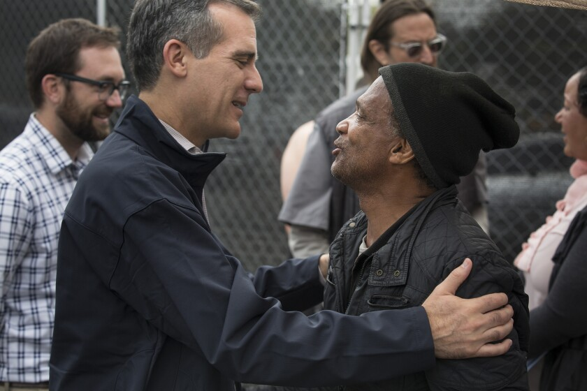 Mayor Eric Garcetti, left, embraces Anthony Hereford, 58, while meeting homeless people at the Center at Blessed Sacrament Hollywood.