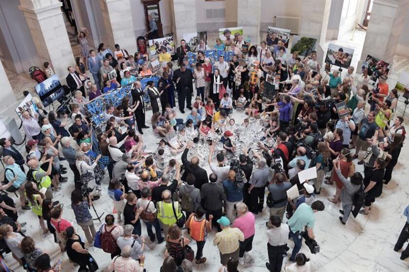 Niños cubiertos con mantas plateadas de emergencia, acompañados por algunos padres, líderes de distintas religiones y activistas de derechos humanos se manifiestan hoy, jueves 21 de junio de 2018, en el edificio Russell del Senado en Washington (Estados Unidos). EFE