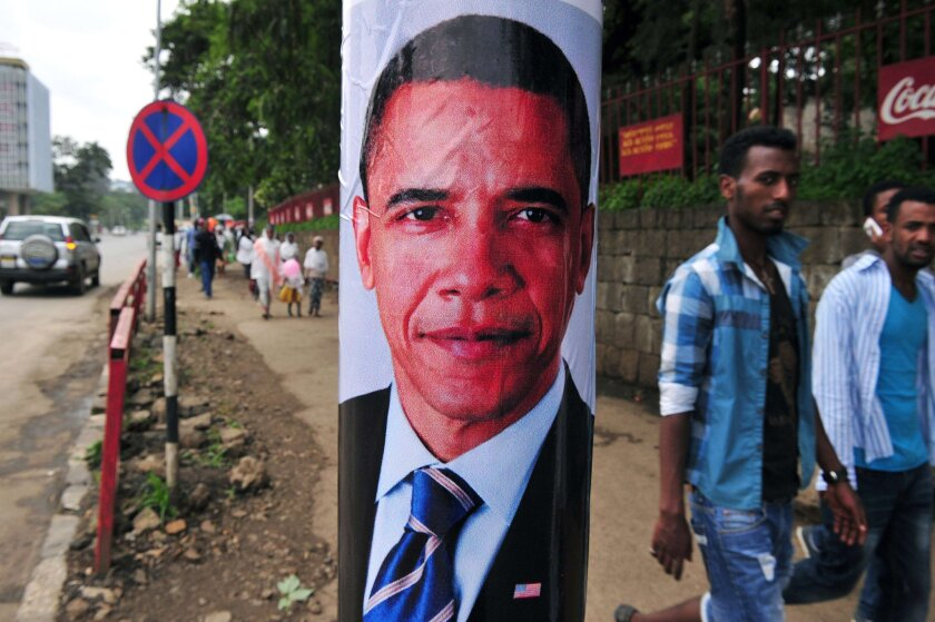 Pedestrians walk past a poster of President Obama before his arrival in Addis Ababa, Ethiopia, on July 26, 2015.
