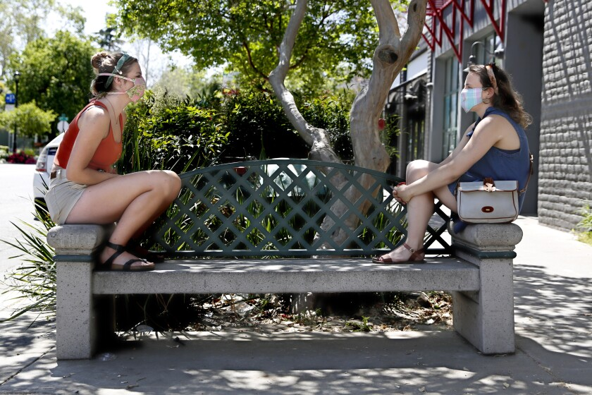 Catie Fee, left, and Vivi Kirsh visit in downtown Davis, Calif.