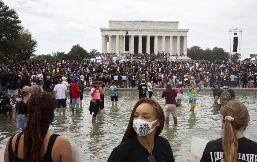 Demonstrators in the Reflecting Pool listen to speakers during the National Action Committee's rally Friday in Washington.
