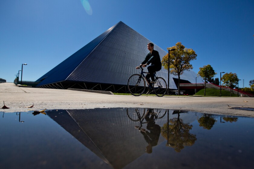 Long Beach, CA., March 11, 2020 - A student bikes pass The Walter Pyramid at Cal State Long Beach, where the campus has gone to online only classes on Tuesday, March 11, 2020 in Long Beach, California. (Jason Armond / Los Angeles Times)