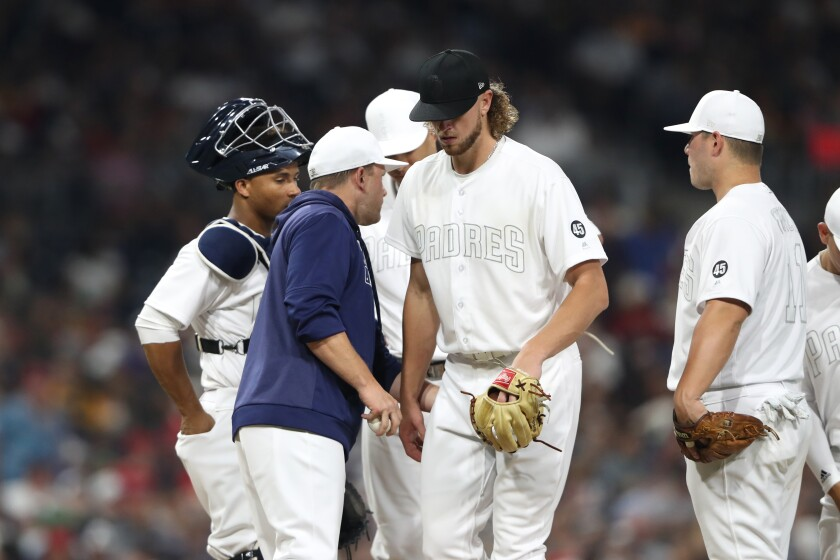 Chris Paddack, middle, walks off the mound after manager Andy Green, with ball in hand, removes him during the third inning of Friday night's game against the Boston Red Sox at Petco Park.