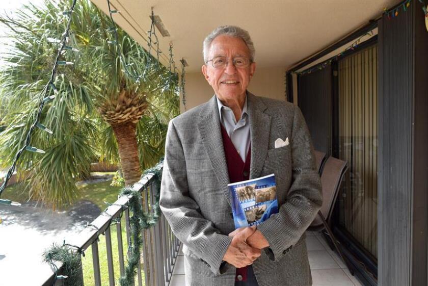"""El documentalista cubano Eduardo Palmer posa mostrando su autobiografía """"Mis 6 guerras"""" durante una entrevista con Efe este 12 de diciembre de 2018 en su casa en Miami, Florida (EE. UU.). EFE"""