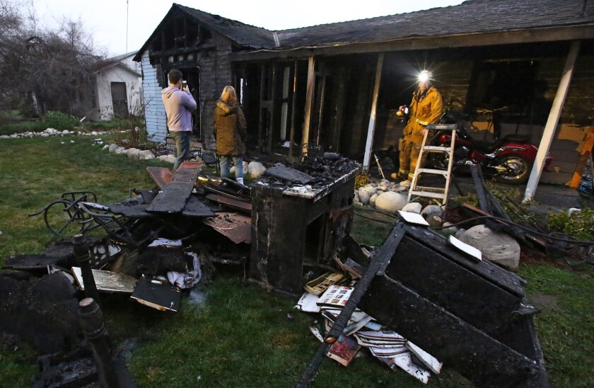 Family members look at the charred remains of their home in Azusa after a fire early Tuesday morning.