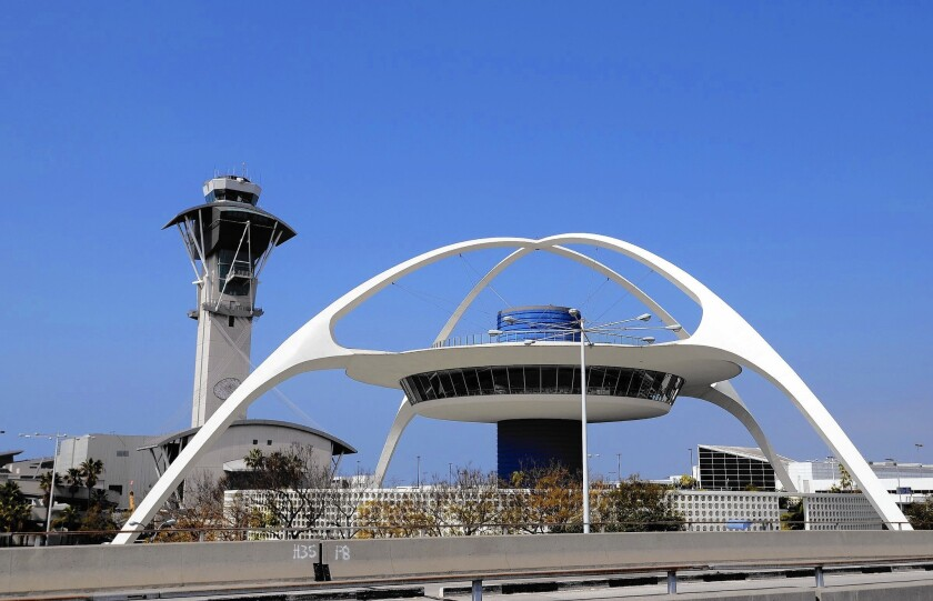 The dropout rate for LAX air traffic controller trainees has been as high as 60%, and many controllers routinely work more than five days a week. Above, the airport's control tower, behind the Theme Building.