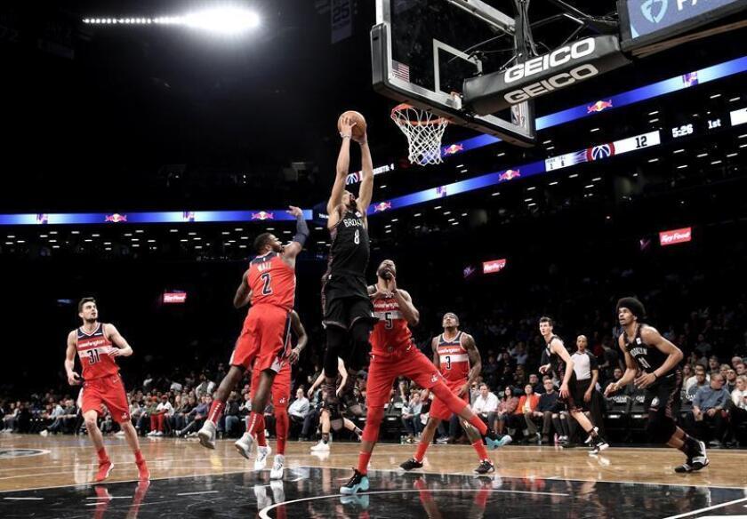 El escolta de los Nets de Brooklyn, Spencer Dinwiddie (C), dispara a más de dos defensores de los Wizards de Washington en la primera mitad del partido de baloncesto de la NBA entre los Washington Wizards y los Nets de Brooklyn en el Barclays Center en Brooklyn, Nueva York, EE. UU., El 14 de diciembre de 2018.(Baloncesto, Estados Unidos, Nueva York) EFE