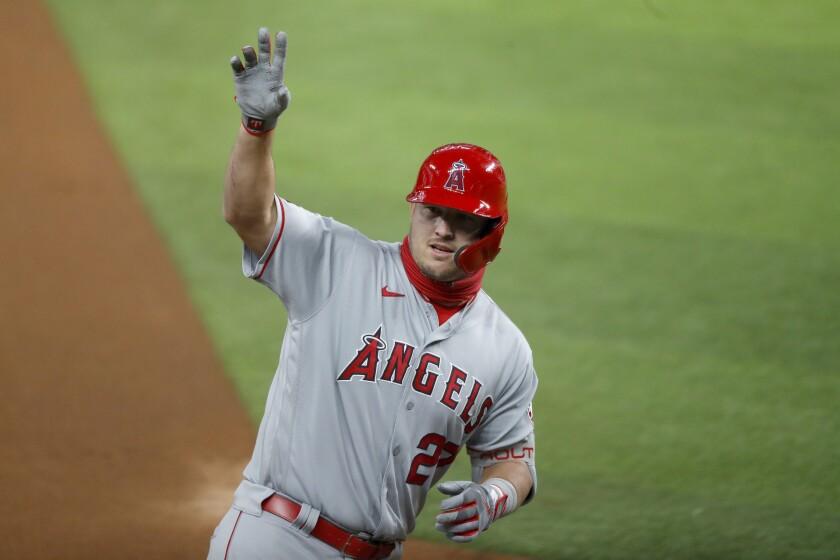 Mike Trout, de los Angelinos de Los Ángeles, saluda a la banca tras batear un jonrón de dos carreras en el primer inning del juego de la MLB que enfrentó a su equipo con los Rangers de Texas, en Arlington, Texas, el 7 de agosto de 2020. (AP Foto/Tony Gutierrez)