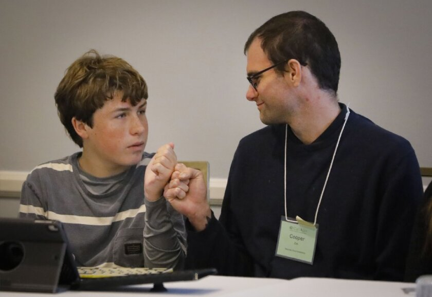 Howard LipinCaption: SAN DIEGO, CA 2/23/2019: Otto Lana, left, and Cooper Zak, right, the social science and english teacher at Sea Change Preparatory, Otto's teacher, fist bump during the The Power of Communication panel at the 36th annual Cal-TASH conference on disability rights at the Town and Country San Diego. Otto has autism and apraxia which prevents him from speaking words with his mouth.