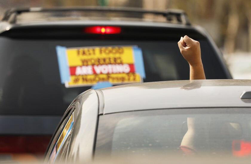 A driver raises a fist out of her sunroof during a protest