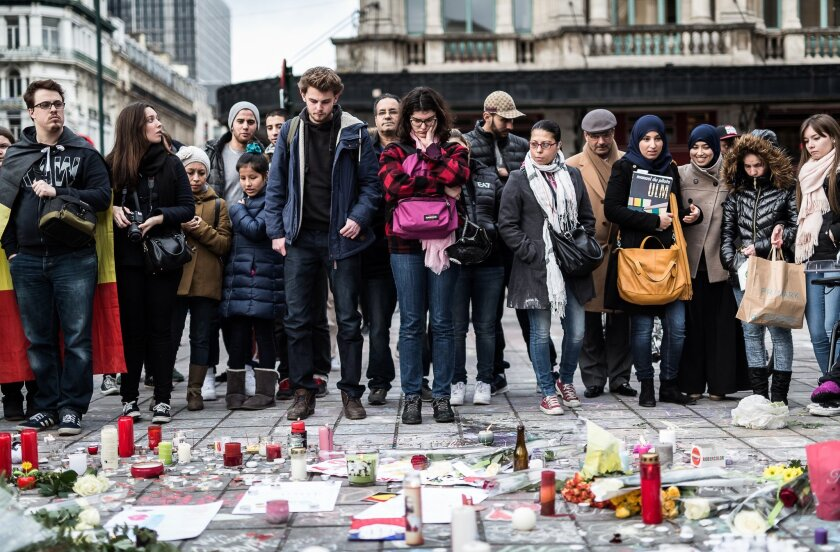 People gather at a memorial for victims of attacks in Brussels on Wednesday, March 23, 2016. Belgian authorities were searching Wednesday for a top suspect in the country's deadliest attacks in decades, as the European Union's capital awoke under guard and with limited public transport after scores were killed and injured in bombings on the Brussels airport and a subway station. (AP Photo/Valentin Bianchi)