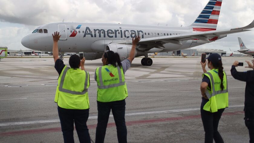 Employees watch as American Airlines Flight 903 prepares for takeoff on Sept. 7, 2016, becoming the first commercial flight from Miami to Cuba in 55 years.