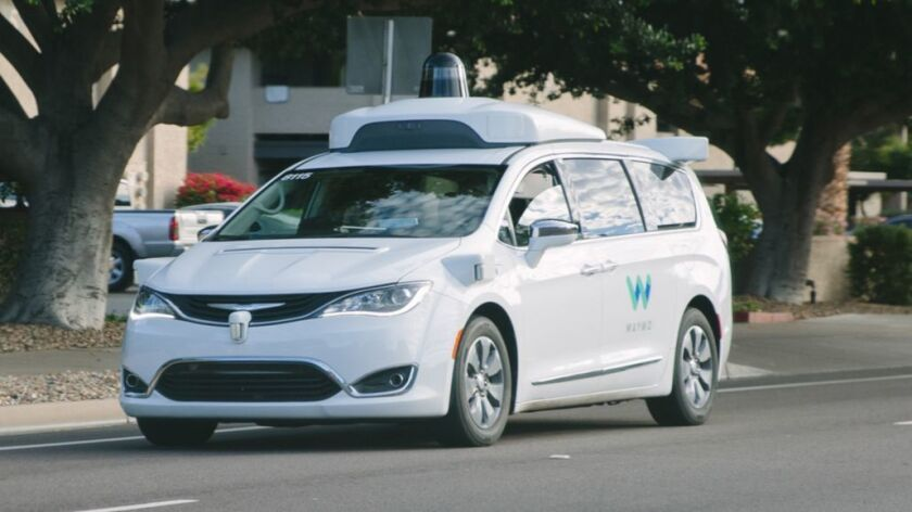 An autonomous Waymo Chrysler Pacifica hybrid van drives in Chandler, Ariz., on Dec. 5.