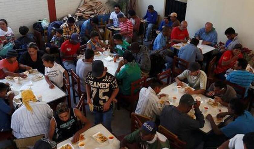 Inmigrantes centroamericanos reciben alimentos hoy, viernes 6 de abril de 2018, en la iglesia Nuestra Señora de la Asunción, de Puebla (México). EFE