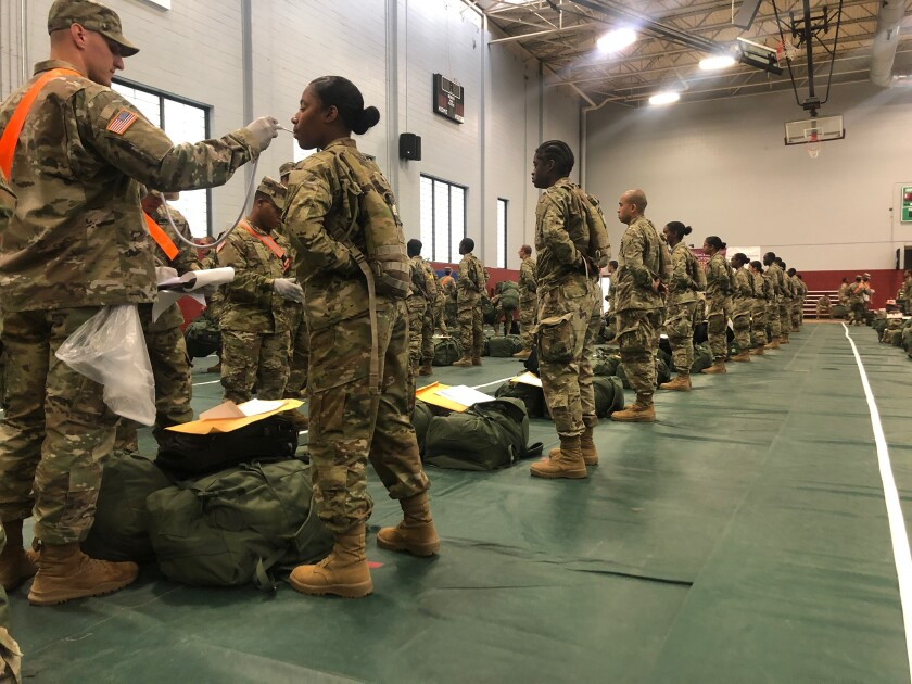 In this image provided by the U.S. Army, recent Army basic combat training graduates have their temperatures taken as they arrive at Fort Lee, Va, on March 31, 2020, after being transported using sterilized buses from Fort Jackson, S.C. COVID-19 has had a dramatic impact on military recruiting, shuttering enlistment stations around the country and forcing thousands of recruiters to woo potential soldiers online. Recruiters have had to abandon their normal visits to high schools and malls, and instead rely almost exclusively on social media to reach young people. (U.S. Army via AP)