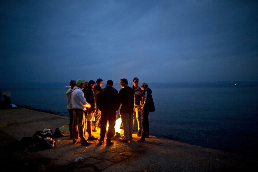 In this Tuesday, Oct. 6, 2015, file photo, Afghan refugees gather around a fire to warm themselves from the early morning cold, after spending the night at a resting point, after arriving on a dinghy from the Turkish coast to the northeastern Greek island of Lesbos. Afghans make up the second large