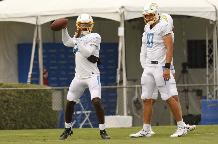 Chargers quarterback Tyrod Taylor throws a pass in practice in front of rookie Justin Herbert